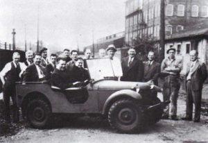 Bantam nr 1 zmontowany  dniu 21 września-1940-roku.-Za kierownicą-dyrektor-fabryki-Harold-Crist,-obok prezes Frank Fenn